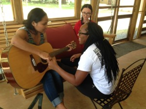 During a few quiet hours the evening before Day 1, Meh Sod teaches Quayneshia a song from Burma as Julia looks on.